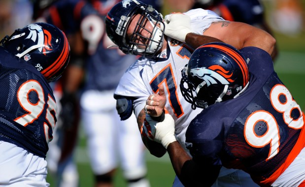 Broncos defensive lineman Ryan McBean (98) drives tackle Clint Oldenburg (71) out of the hole during training camp at Dove Valley on Aug. 11, 2009.