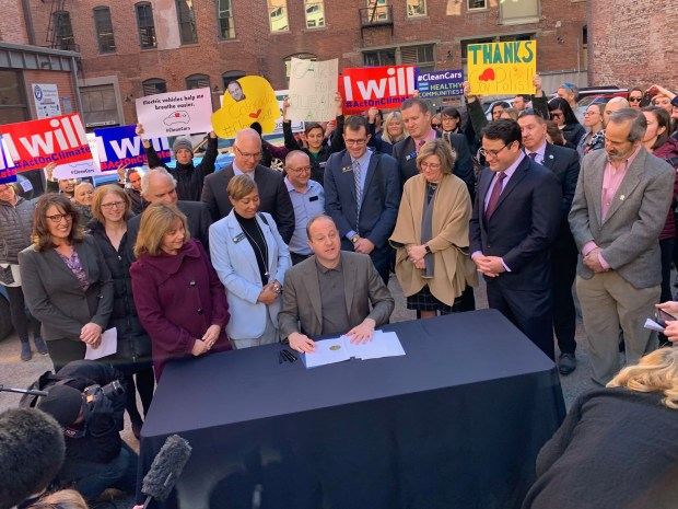 Colorado Gov. Jared Polis, center, signs an executive order promoting zero emission vehicles Thursday in downtown Denver.
