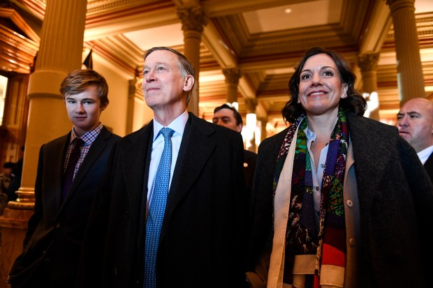 Outgoing governor John Hickenlooper stands with ...