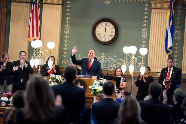 Gov. Jared Polis waves after delivering ...