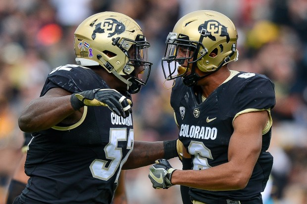 Defensive end Leo Jackson III (52) and defensive back Evan Worthington (6) of the Colorado Buffaloes celebrate a defensive play against the California Golden Bears at Folsom Field on Oct. 28, 2017 in Boulder.