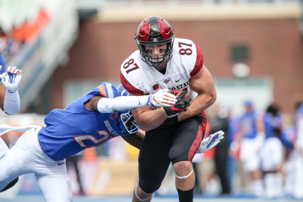 Tight end Kahale Warring (87) of the San Diego State Aztecs runs for the end zone through the tackle of corner back Avery Williams (26) of the Boise State Broncos during first half action on Oct. 6, 2018 at Albertsons Stadium in Boise, Idaho.