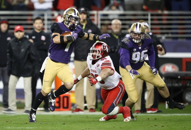 Byron Murphy (1) of the Washington Huskies runs past Cole Fotheringham (89) of the Utah Utes to return an interception for a touchdown during the Pac 12 Championship game at Levi's Stadium on Nov. 30, 2018 in Santa Clara, Calif.