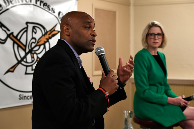 Denver Mayor Michael Hancock, left, responds ...