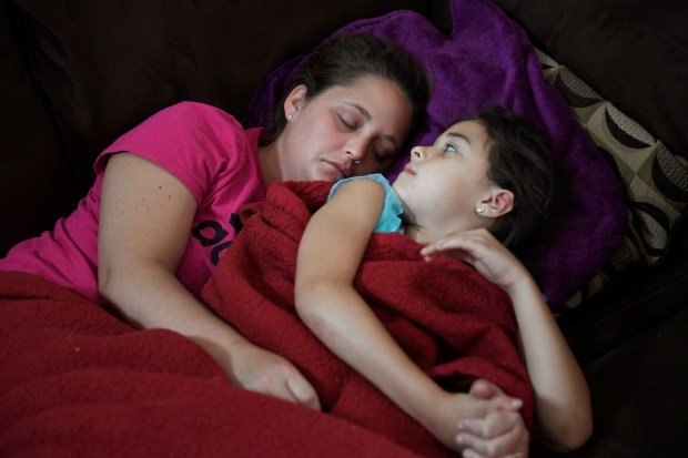 Mackenzie, 7, rests with her mother ...