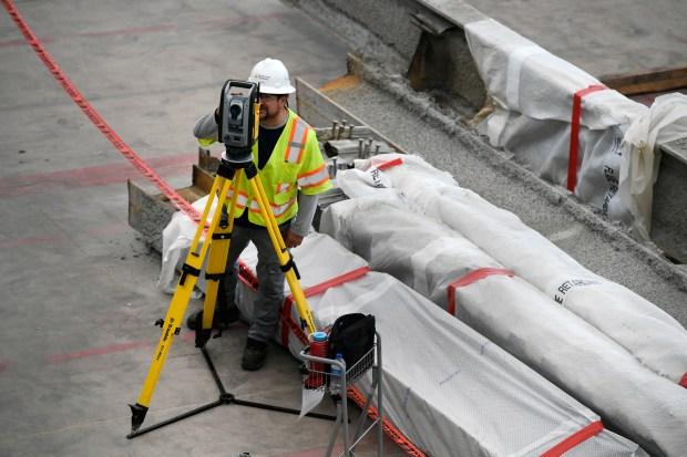 A construction worker surveys an area ...