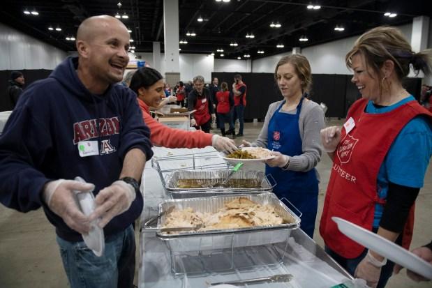 Salvation Army volunteers laugh while preparing ...
