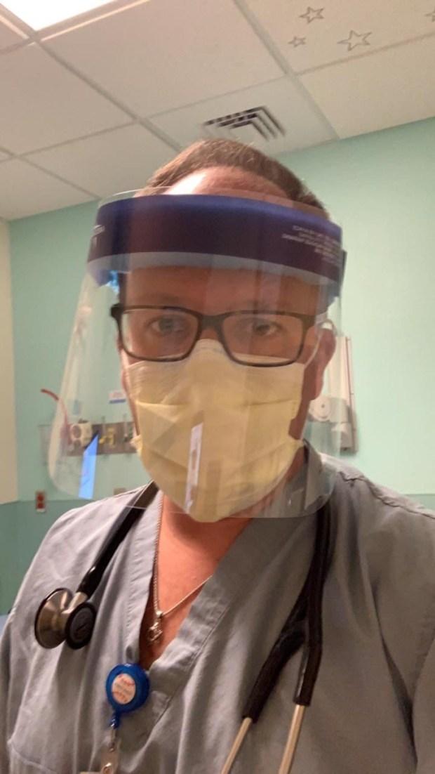 Dr. Matthew Harris wearing a face ...