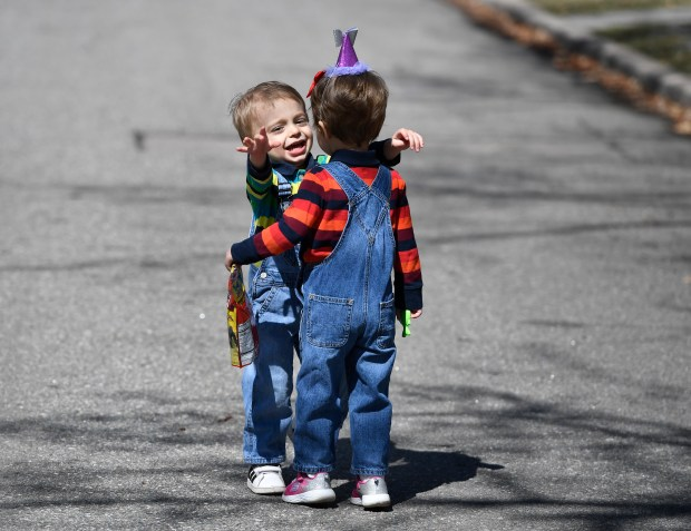 Max Freed, 3, left, gives his ...