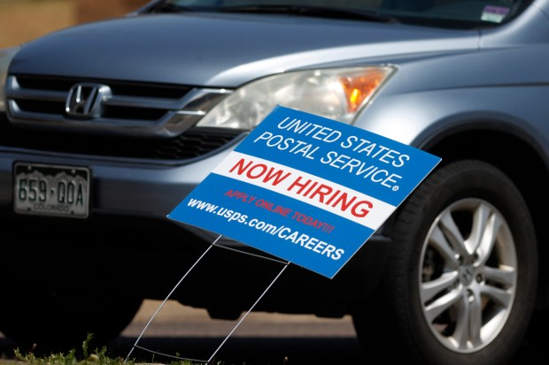 A hiring sign stands outside a ...