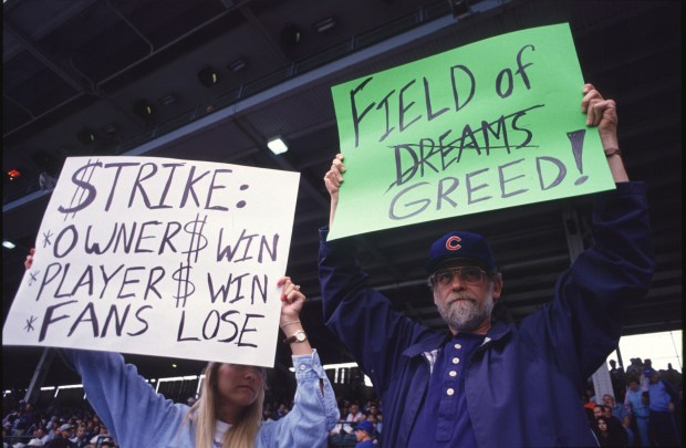 Fans hold up signs in protest ...