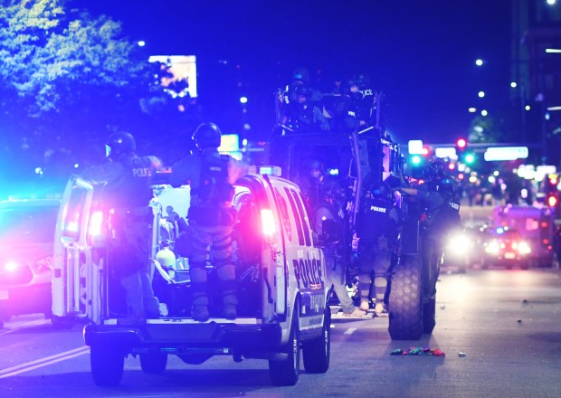 Police move down Colfax Avenue during ...