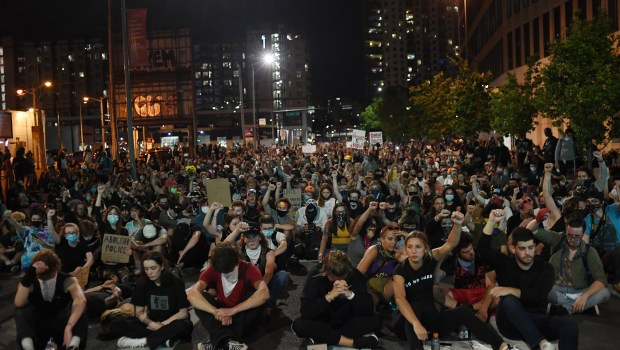 Protesters stop marching and sit in ...