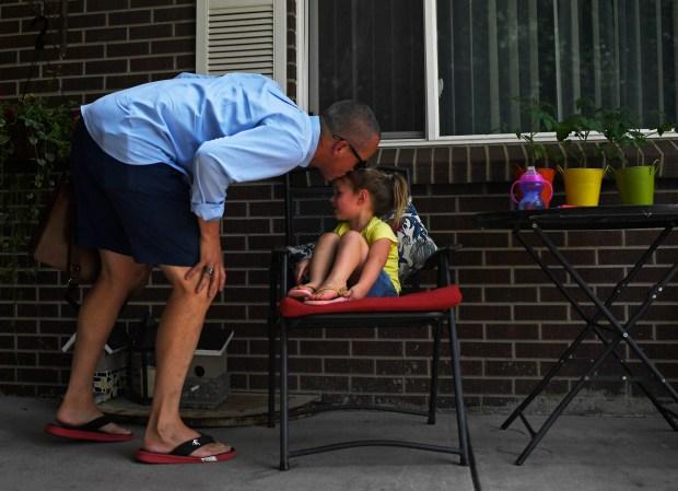 Greg Nidy kisses his daughter Cora ...