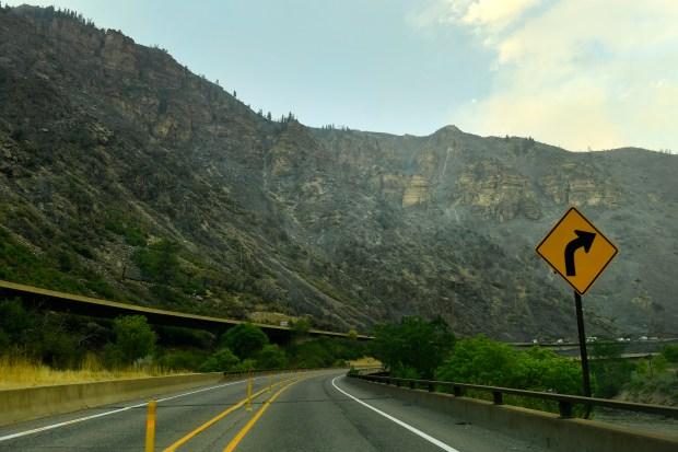 Smoke smolders along the steep rocky ...
