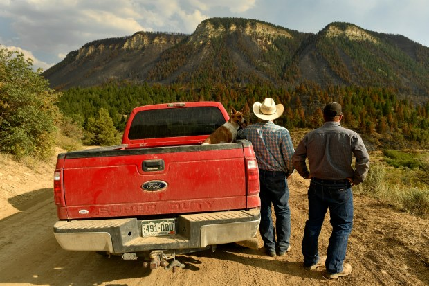 Longtime rancher Todd Brackett, center, his ...