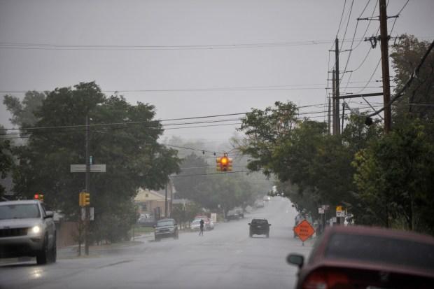 Rain falls as a pedestrian and ...