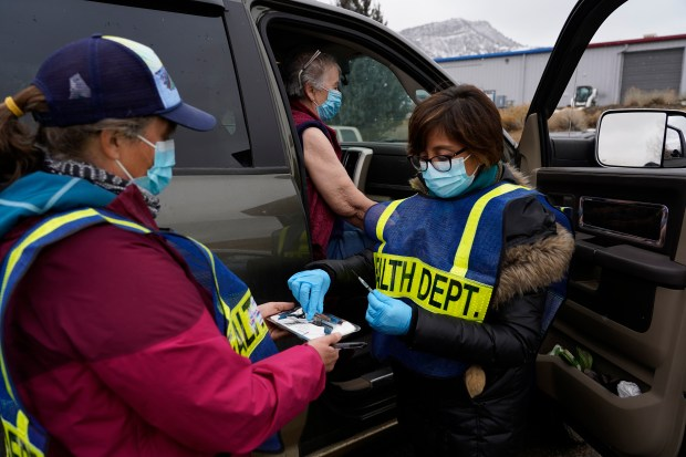 Becca Arndt, left, and Christy Deem, right, prepare to administer a COVID-19 vaccine to Betty Hadden of Red Mesa, Colorado, during a drive-up vaccination clinic at San Juan Basin Public Health in Durango on Feb. 12, 2021.