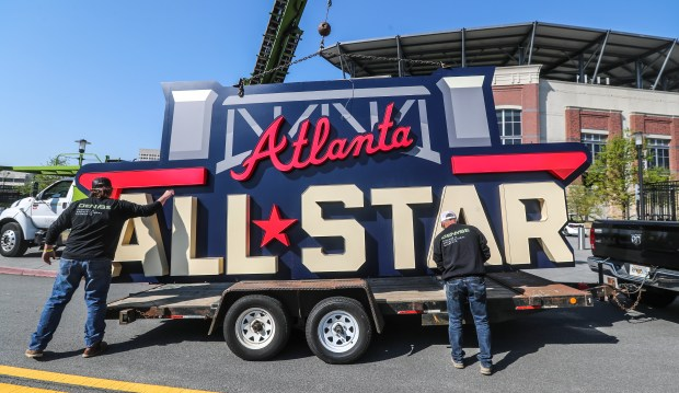 Workers load an All-Star sign onto ...