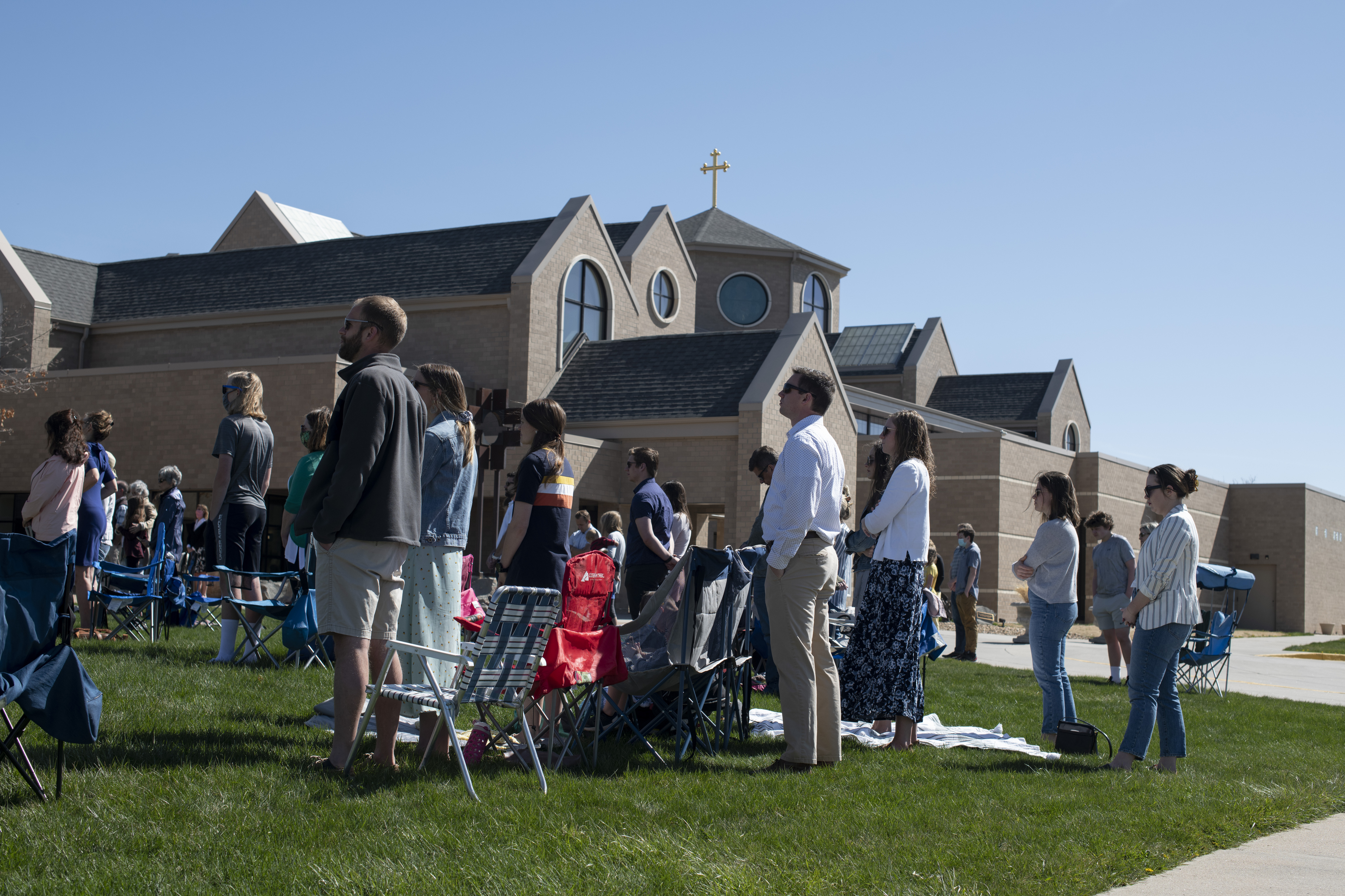 Parishioners attending the outdoor Mass stand ...