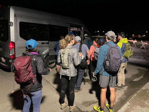 Hikers wait in Breckenridge for a ...