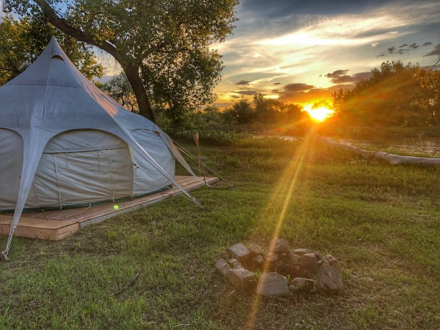 A large canvas-sided Lotus Belle yurt sits on a wooden platform near a river at Platte River Fort near Greeley, offering a comfortable camping experience.