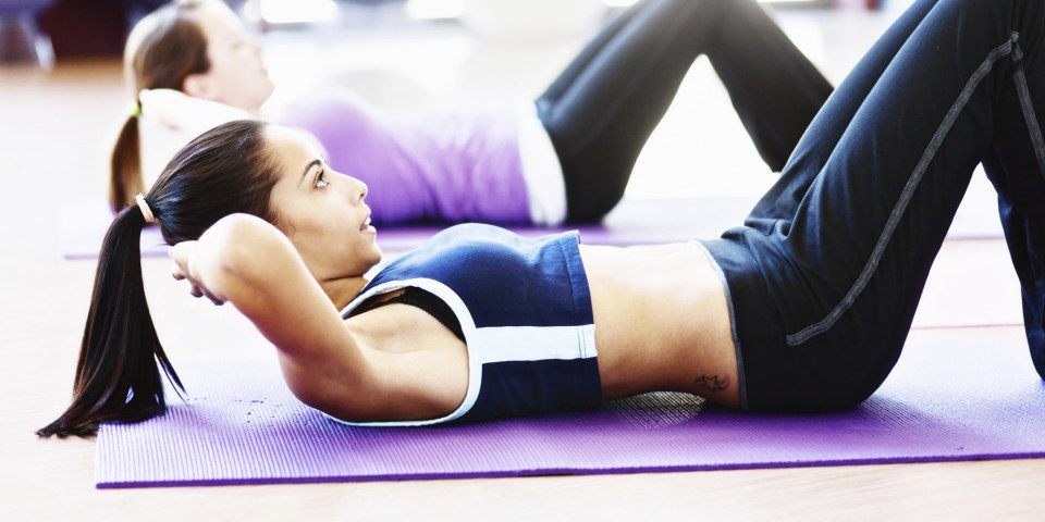 Getting fit can be tough: young women doing sit ups