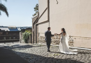 Bride and Groom walk down an alley in The Rocks, Sydney, under the afternoon sunlight