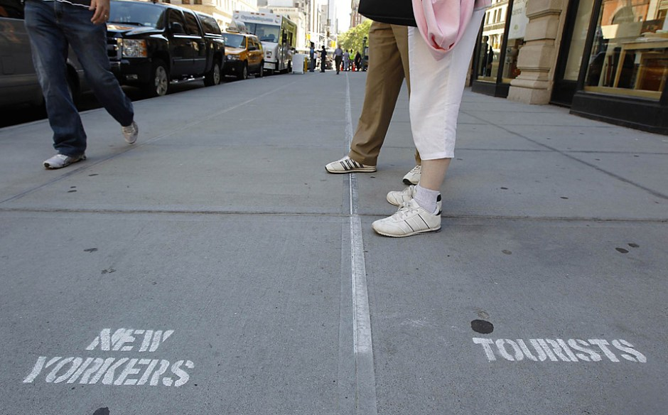 Two tourists stand on a sidewalk along Fifth Avenue in New York City