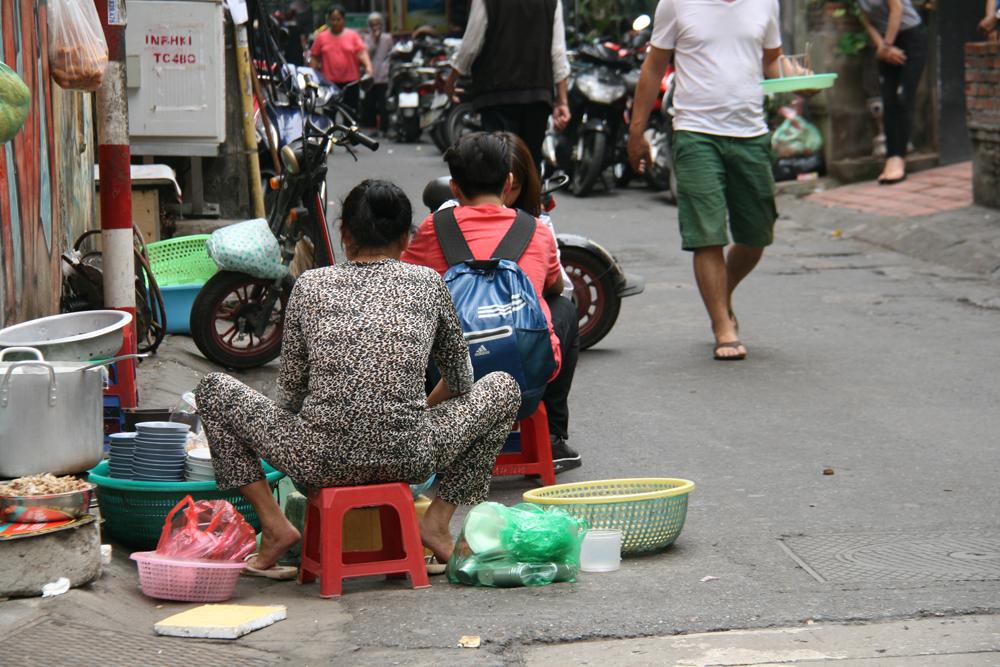 Femme faisant la vaisselle dans la rue à Hanoï