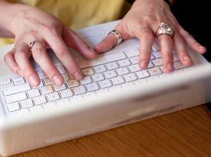 Manos masculinas sobre teclado blanco