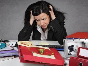 Mujer desesperada en su escritorio de trabajo llena de carpetas