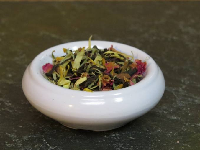 A small white bowl on a green stone table. The bowl is filled with calendula petals, rose petals, black tea, and vanilla.