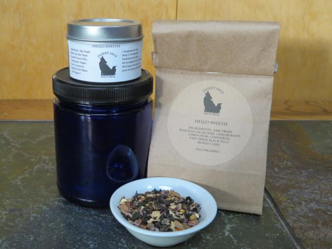 Small white bowl of chocolate chili chai. Behind it are a blue glass jar, a silver sample tin, and a tintie bag.