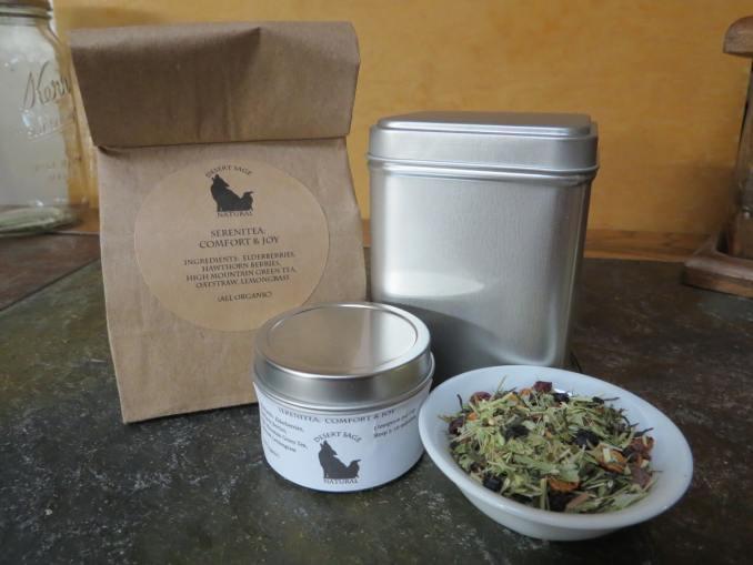 Bag, Sample Tin, Tin for Tea. Small white bowl of herbal tea.