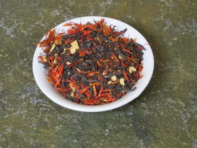 A small white bowl full of a blend of black tea, rosehips, ginger, and safflower. It is set on a green textured stone table.