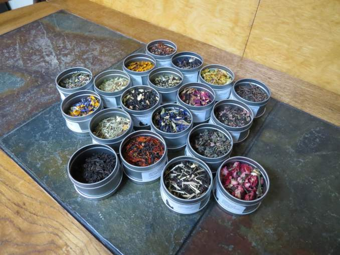 Array of open sample tea tins with a riotous rainbow of colour represented.