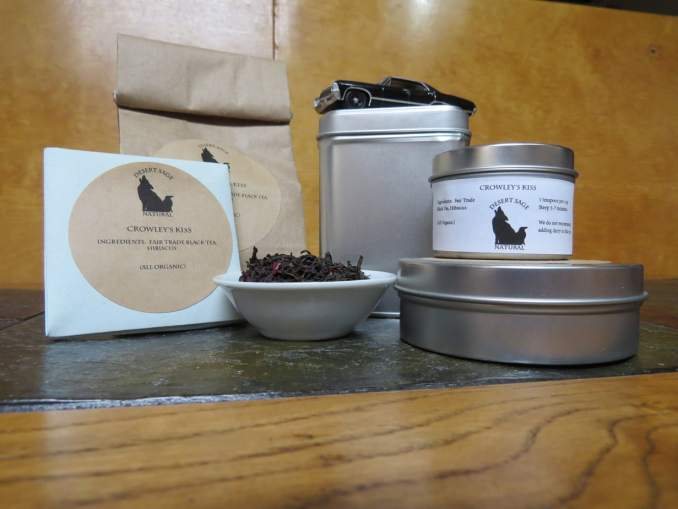 """A small white bowl full of a blend of hibiscus flowers and black tea. It is surrounded by an array of tea tins, a small origami packet of a size to hold a single teabag, and a bag of tea. The Supernatural Impala is perched atop the largest tin. The labels read: """"Crowley's Kiss, Ingredients: Fair Trade Black Tea, Hibiscus Flowers, (All Organic)"""""""