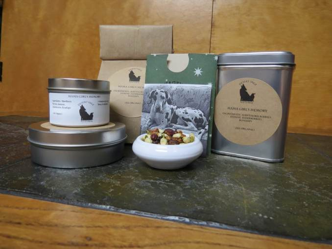 "A small white bowl filled with a blend of jasmine flowers, hawthorn berries, elderberries, and rosehips. Set just behind it is a black and white photo of a white and black harlequin Great Dane. Arrayed around the bowl and picture are tea tins and a bag of tea. The labels read: ""Mama Girl's Memory, Organic Ingredients: hawthorn Berries, Jasmine, Elderberries, Rosehips, (All Organic)"" The table they sit on is a green textured stone, and there is a light woodgrain behind."