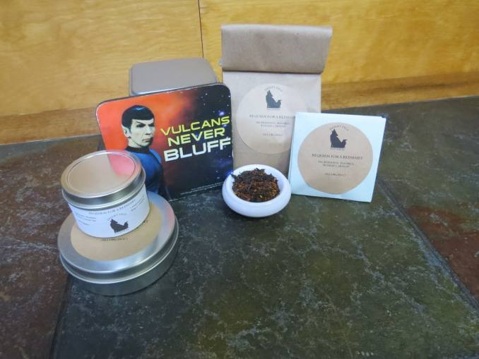 "A small white bowl full of a blend of Russian Caravan and Rooibos. Arrayed around it are a couple of sample tea tins, a larger tea tin, a bag of tea, a small origami packet of a size to fit a teabag, and a coaster with an image of Spock and the words ""Vulcan's Never Bluff."" The labels read: ""Requiem for a Redshirt, Ingredients: Rooibos, Russian Caravan, (All Organic.)"" The table is green textured stone, and the background is a light woodgrain."