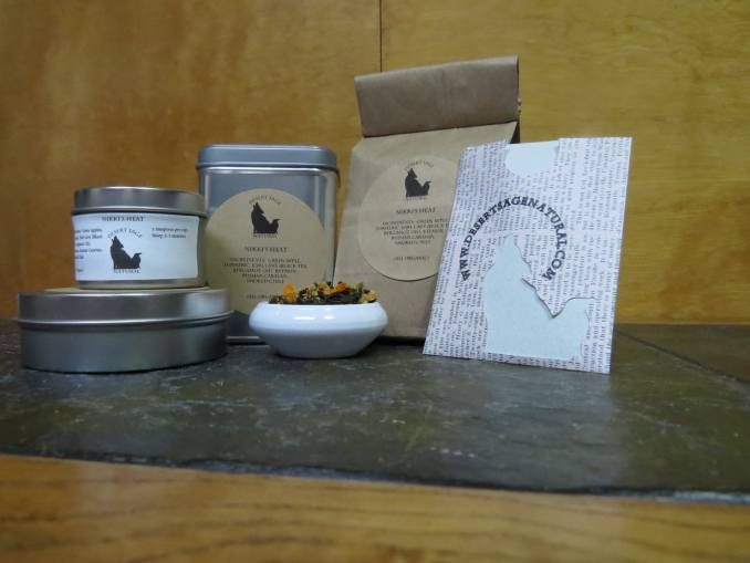"A small white bowl filled with a blend of black teas, bits of dried turmeric and green apple, and chile flakes. It is surrounded by an array of tea tins, a bag of tea, and a stiff paper packet of a size to hold a teabag. The labels read: ""Nikki's Heat, Keemun, Earl Grey, Dried Green Apple, Russian Caravan, Turmeric, Smoked Chile, (All Organic)"""