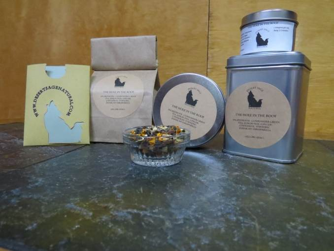 """A small bowl on a green textured stone table. The bowl is filled with a blend of gunpowder green tea, turmeric, ginger, cinnamon, sarsaparilla, and lemon peel. Behind the bowl are 3 tins in various shapes and sizes, a bag of tea, and a cardboard packet with the Desert Sage Natural logo, of a size to hold a single teabag. The labels read: """"The Hole in the Roof, Ingredients: Gunpowder Green Tea, Ginger, Lemon Peel, Turmeric, Cinnamon, Jamaican Sarsaparilla, All Organic"""""""