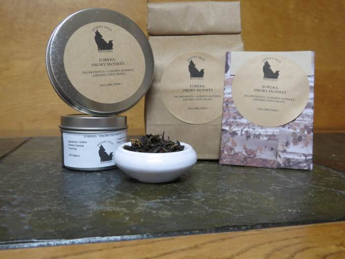 "A small white bowl full of a blend of golden and black teas. It is surrounded by a couple of tea tins, a bag of tea, and a rectangular packet that could hold a teabag. The labels read: ""Eureka: Smoky Monkey, Ingredients: Lapsang Souchong, Golden Monkey, (All Organic.)"