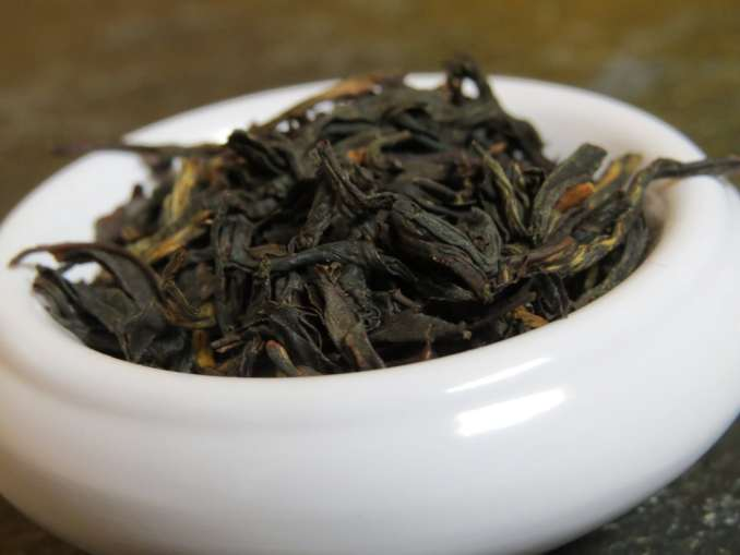 Closeup shot of a blend of black and golden teas in a small white bowl. Can see a little bit of textured stone in the background.