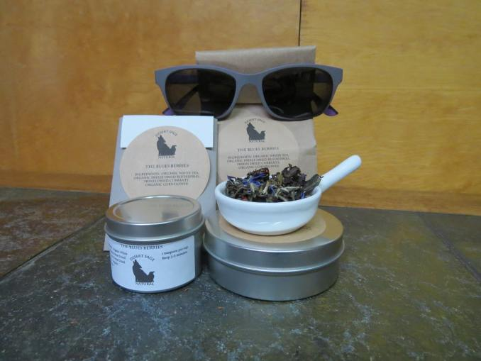 """Two tins, one tall and thin, one short and wide, next to each other. The thinner tin has a small white bowl with a blend of white tea, blueberries, currants, and cornflower. Behind those are a rectangular packet that would hold a teabag, and a bag of tea. The labels read: """"The Blues Berries, Ingredients: Organic White Tea, Organic Freezedried Blueberries, Freezedried Currants, and Organic Cornflower."""" The bag of tea is wearing a pair of grey sunglasses."""