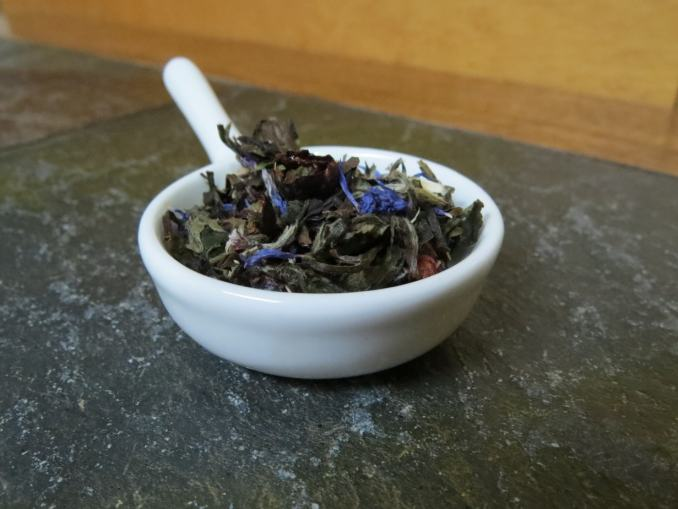 A small white bowl shaped like a pan, set on a textured stone and wood table, filled with a blend of white tea, cornflower, blueberries, and currants.