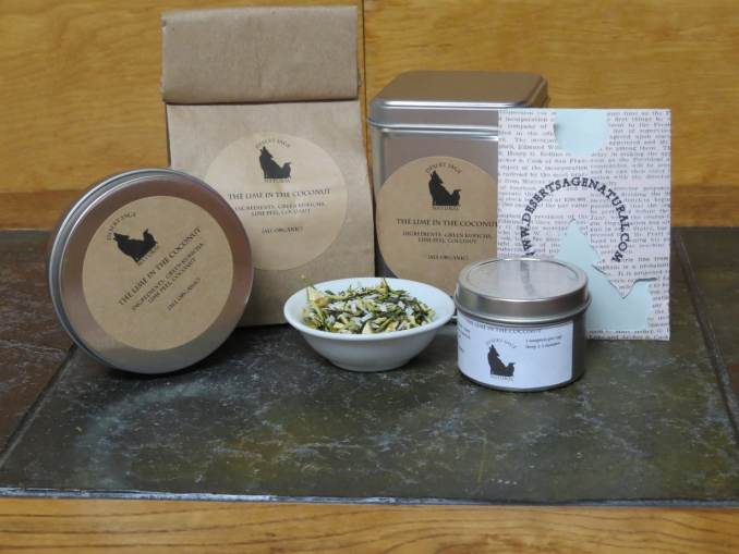 """A small white bowl filled with a blend of green tea, coconut, and lime peel. It is surrounded by a variety of tea tins, a bag of tea, and a small rectangular packet that could hold a teabag. The labels read: """"The Lime in the Coconut, Ingredients: Green Kukicha, Coconut Flakes, Lime Peel, (All Organic)"""""""