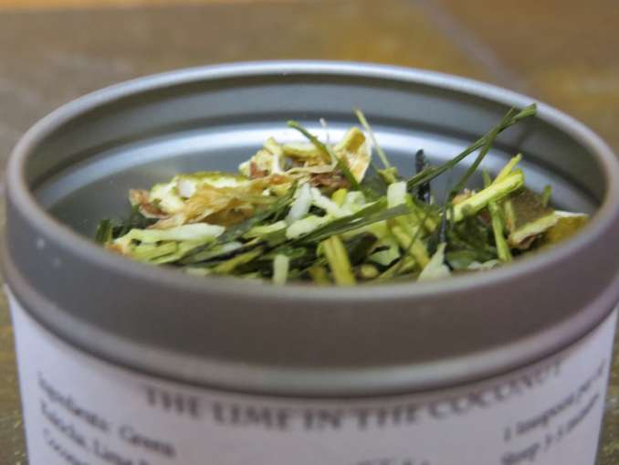 """The picture is zoomed in on the upper edge of a small metal tin. Inside is a blend of green tea, coconut, and lime peel. You can just barely see the top of the label that states """"The Lime in the Coconut."""""""