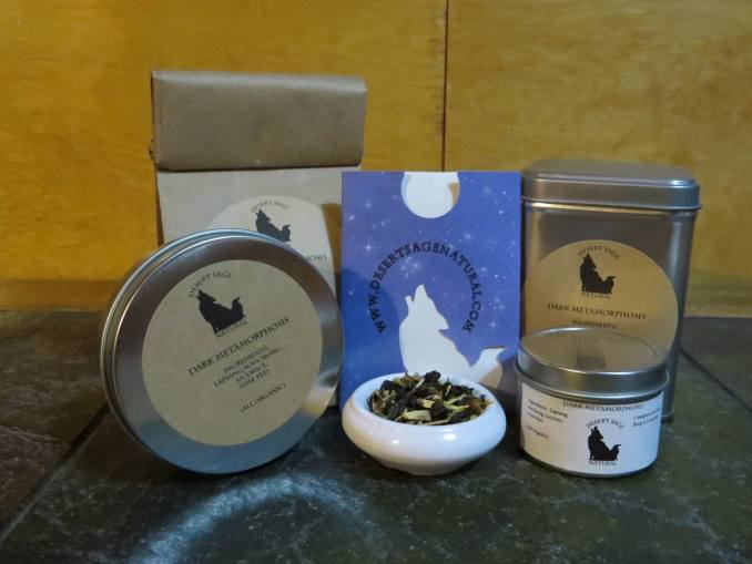 """A small white bowl full of a blend of lapsang, licorice, and lime peel is in the center of an array of tea tins, a bag of tea, and a small paper packet with the desert sage natural logo on it that would hold a teabag. The labels read: """"Dark Metamorphosis, Ingredients: Lapsang Souchong, Licorice, Lime Peel (All Organic)"""""""