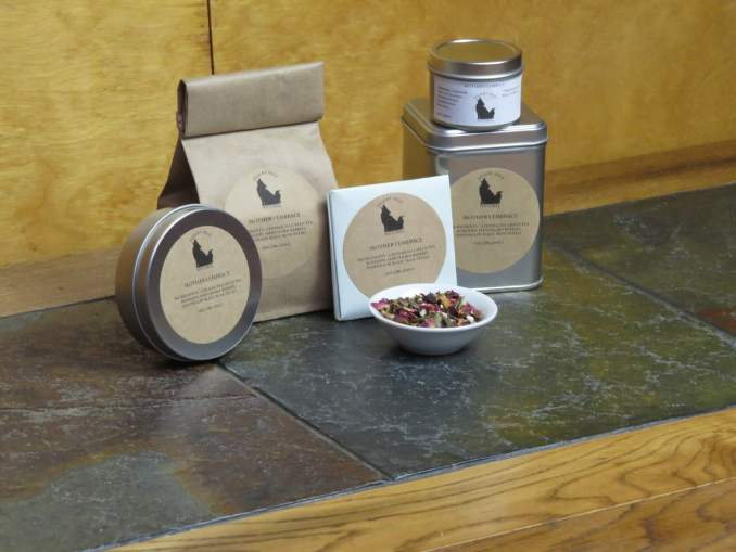 "A small white bowl full of a blend of genmaicha, hawthorn berries, dandelion root, rosehips, and rose petals. It is surrounded by an array of tea tins, a bag of tea, and a small origami packet that could hold a teabag. The labels read ""Mother's Embrace, Ingredients: Genmaicha Green Tea, Rosehips, hawthorn berries, Dandelion Root, and Rose Petals. All Organic."""